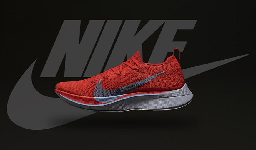 A red tennis shoe with the Nike swoosh and Nike logo on the black background -