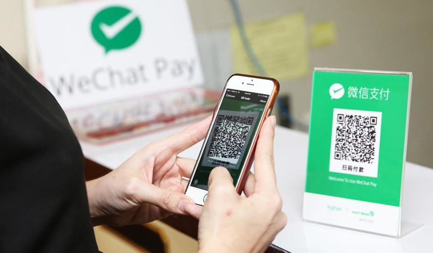 Hands holding a phone that is taking a picture of a QR code with Chinese text above it. In the background, the WeChat Pay logo - Absolunet eCommerce Trends