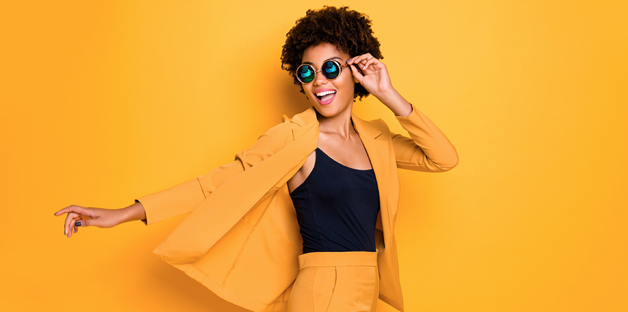 A woman wearing a yellow suit and cool sunglasses. She is pointing to the side. There is a yellow background, the same color as her suit - Absolunet eCommerce Trends
